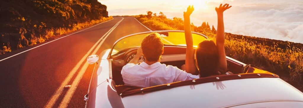 Two people driving convertible
