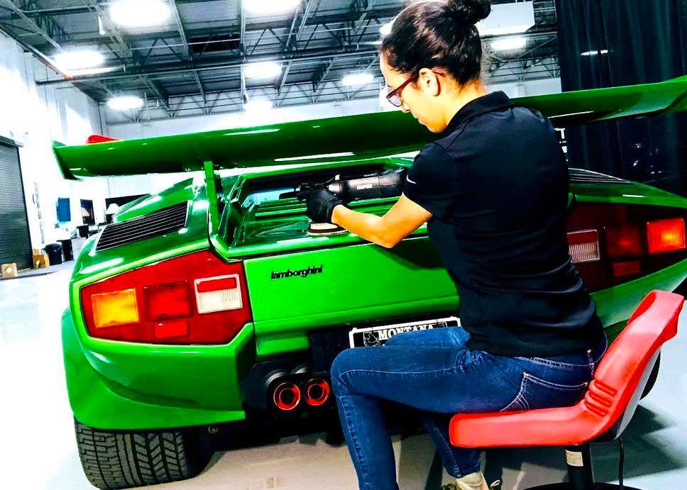 Girl washing and waxing luxury car