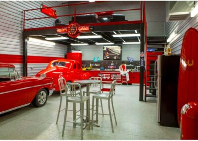 A Toy Barn Custom Car Condo for Performance Enthusiasts Include Custom Cabinetry and Mezzanine